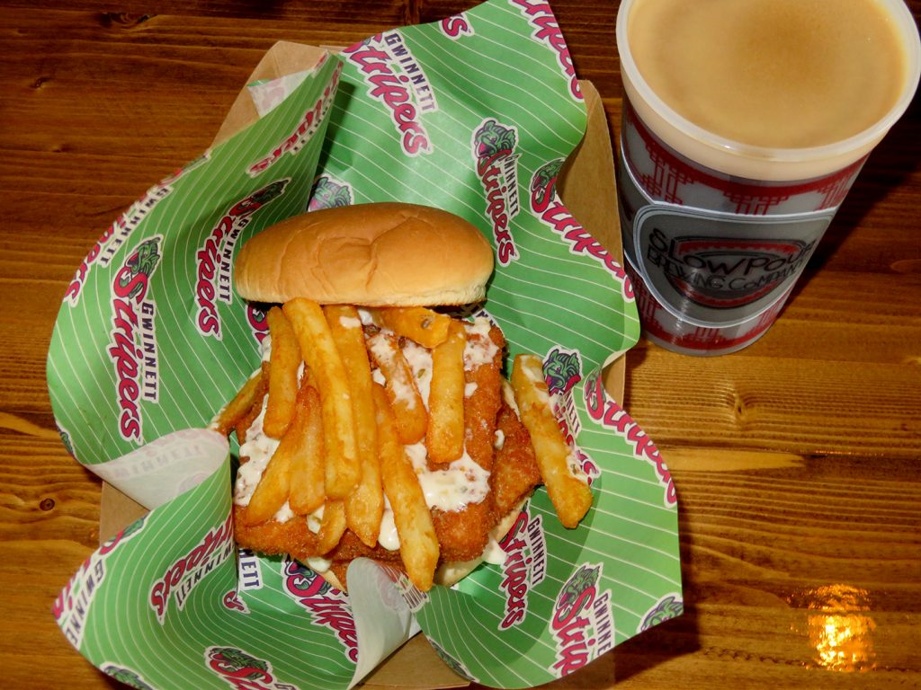 Double-stacked fish sandwich topped with French fries in a basket next to a plastic cup with beer.