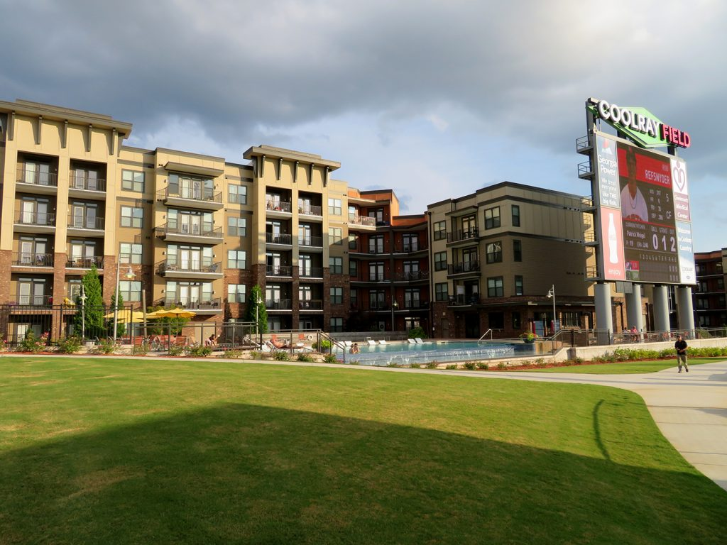 "Large apartment building with pool in front of it behind a large scoreboard that says ""Coolray Field."""