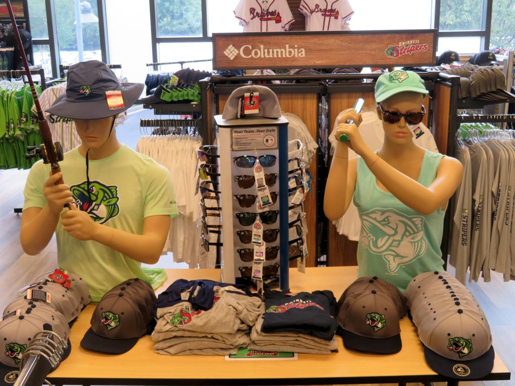 A male mannequin on the left holds a fishing pole and a female mannequin on the right holds a miniature baseball bat in a fishing motion.