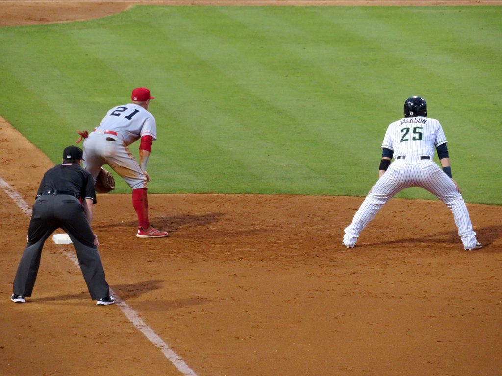 Gwinnett Stripers player Alex Jackson leads off first base during a game.