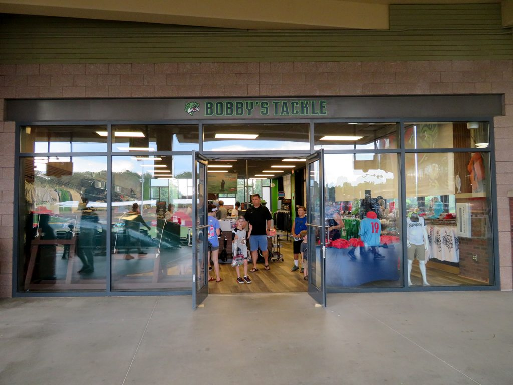 "Glass doors open to a merchandise store with ""Bobby's Tackle"" written above the entrance."