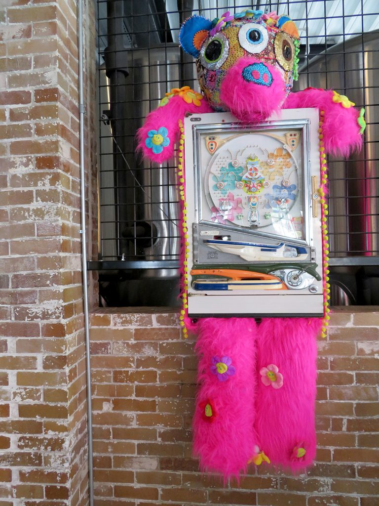 An old pachinko machine converted to art with bright pink fuzzy head, arms, and legs.