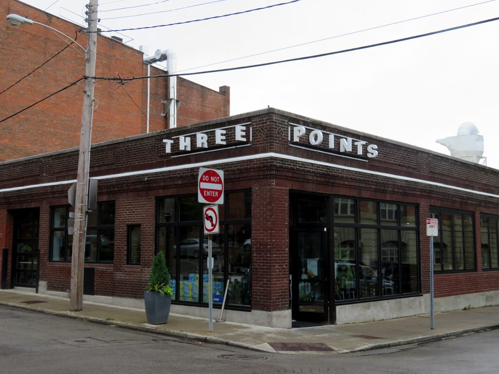 "Diagonal view of brick building with large windows and text that says ""Three Points"" near the roof line."