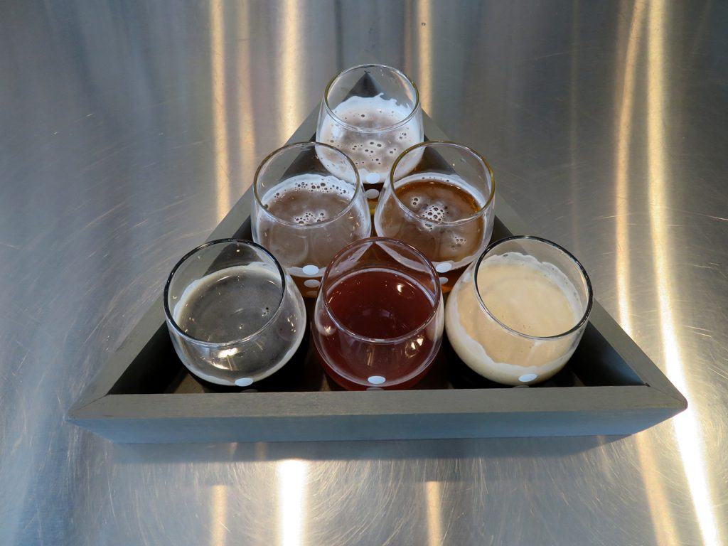 A flight of six beer tasting glasses stacked in a triangle at 3 Points Urban Brewery.