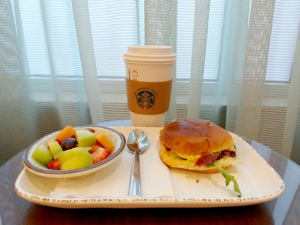 Try on top of a table with a small bowl of fruit on left, a 20-ounce Starbucks cup of coffee in the middle, and a breakfast sandwich on the right at the Courtyard Indianapolis Downtown.