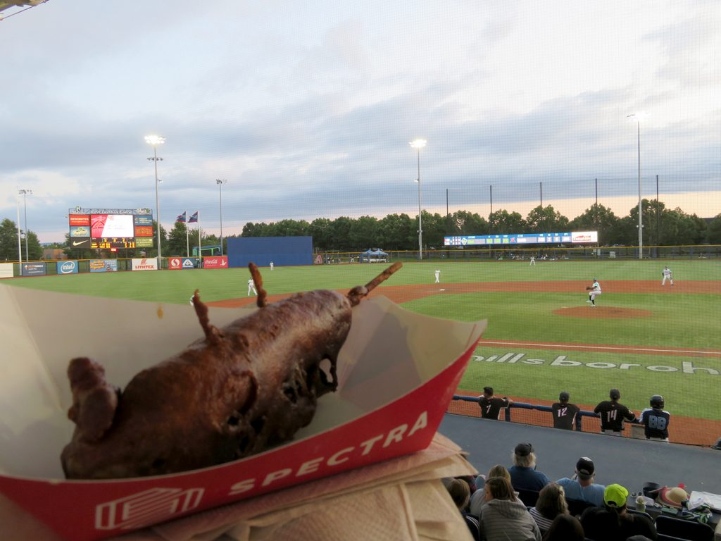 A deep fried chile relleno corn dog in paper basket with a baseball field in the background.