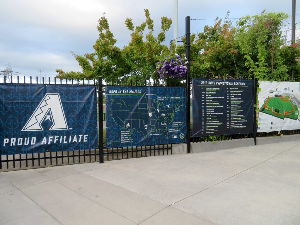 "Four banners attached to a metal fence with different information including one that says ""Hops in the Majors"" with a map of the United States."