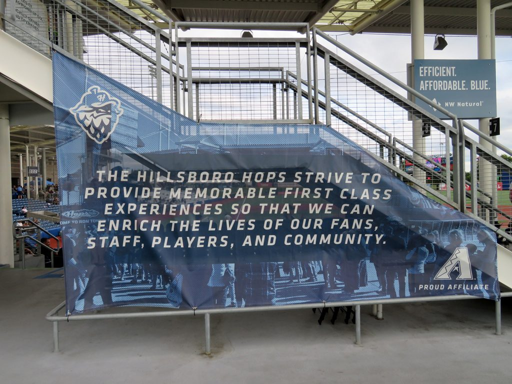 "A banner on a set of stairs that says ""The Hillsboro Hops strive to provide memorable first class experiences so that we can enrich the lives of our fans, staff, players, and community."""