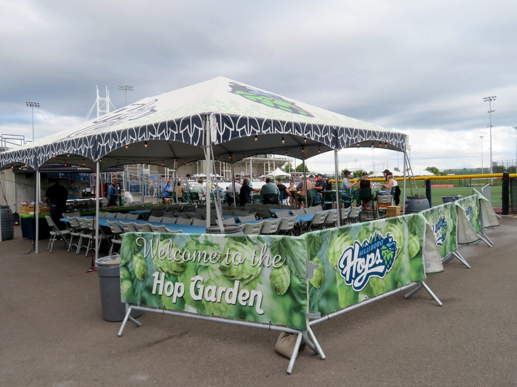 "A large canopy tent towers over multiple tables and chairs with a steel fence wrapped with a banner that says ""Welcome to the Hop Garden."""