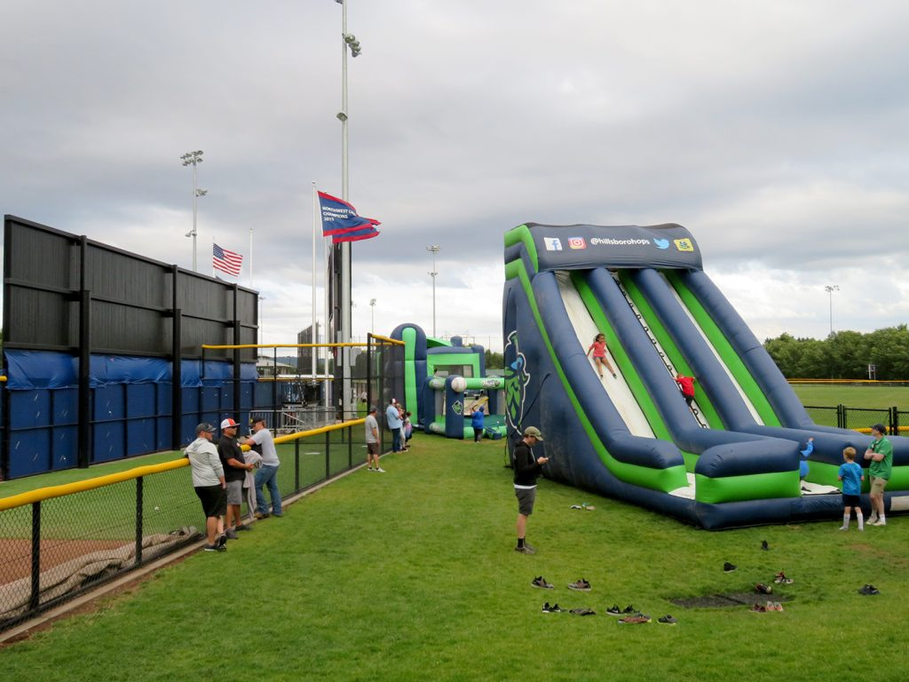 Kids slide down a large inflatable slide in the center while another kid throws a pitch at an inflatable game in the background.