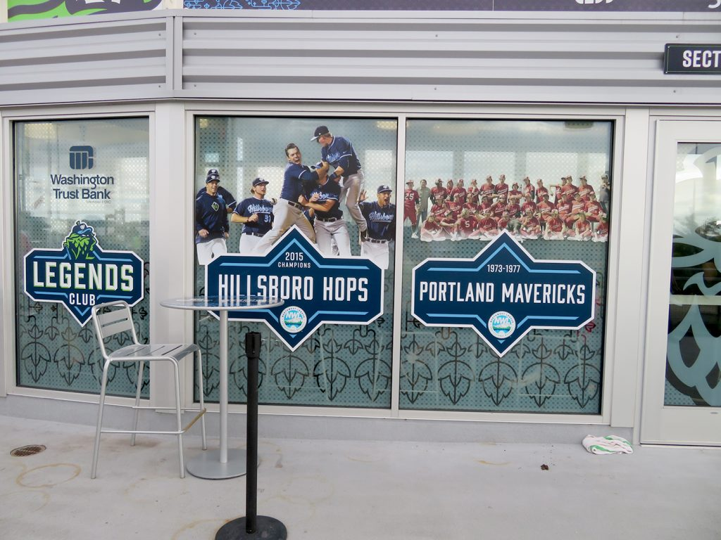"Glass windows with cling wrap designs that say ""2015 Champion Hillsboro Hops"" and another that says ""1973-1977, Portland Mavericks."""