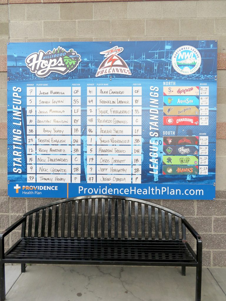 A large board with starting lineups for the Hillsboro Hops and Salem-Keizer Volcanoes written out by hand.