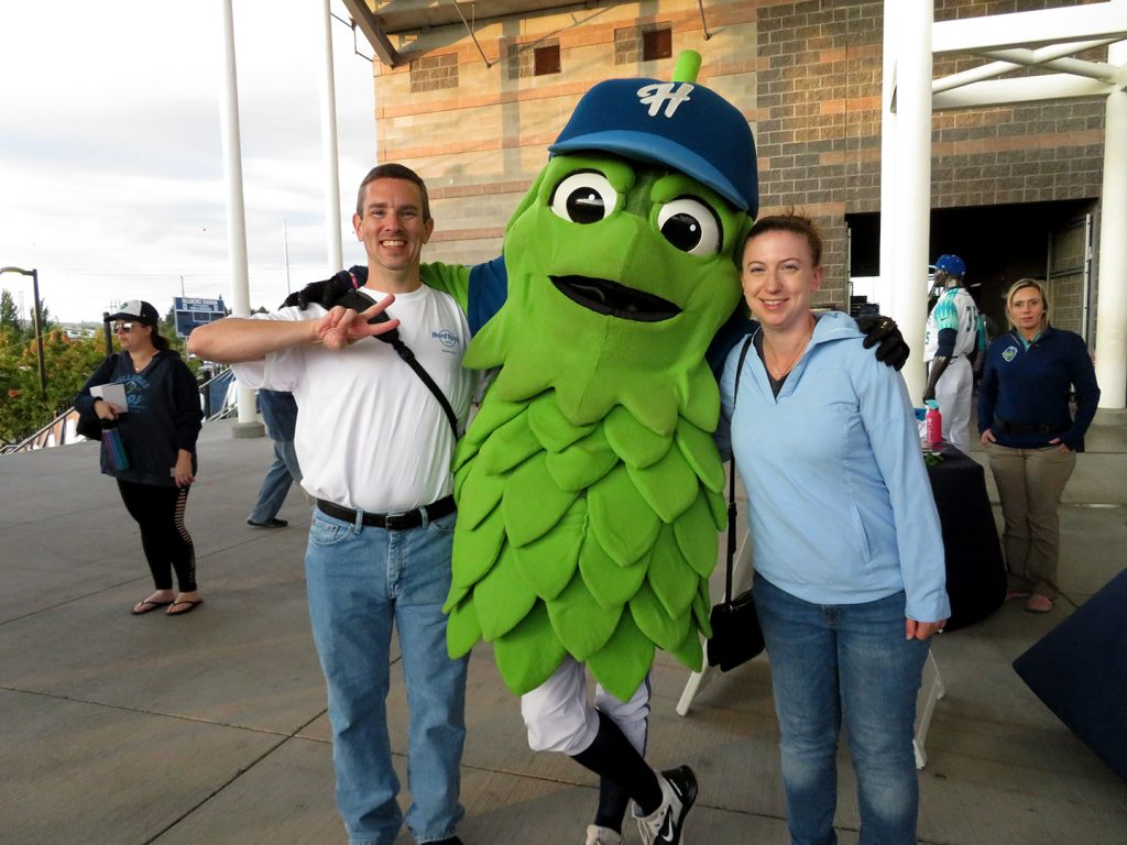 A man and woman stand with an anthropomorphic hop named Barley.