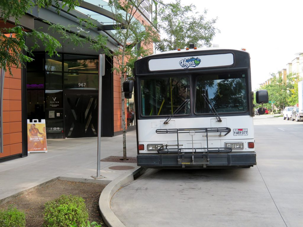 "A large white bus with a ""Hillsboro Hops"" logo on top of it waits next to a curb."
