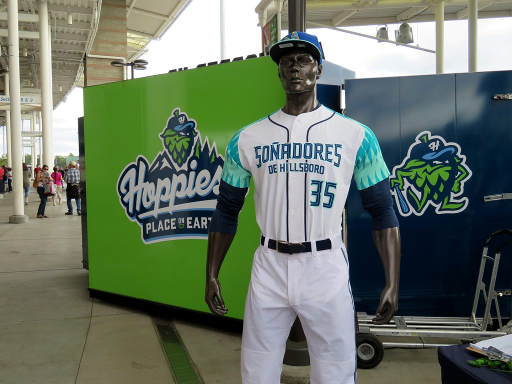 "A grey mannequin wearing a baseball jersey that says ""Mannequin in Soñadores de Hillsboro"" with teal and turquoise sleeves."