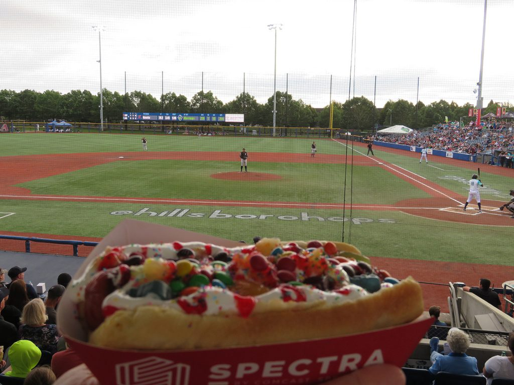 A hot dog topped with marshmallow creme, crushed pineapple, strawberry puree, fruity snacks, miniature M and M's, and rainbow sprinkles with a baseball field in the background.