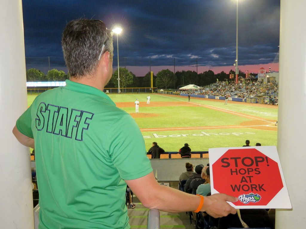 "A man in a green shirt that says ""Staff"" on the back holds a cardboard sign that with a red stop sign design that says ""Stop! Hops at work."""