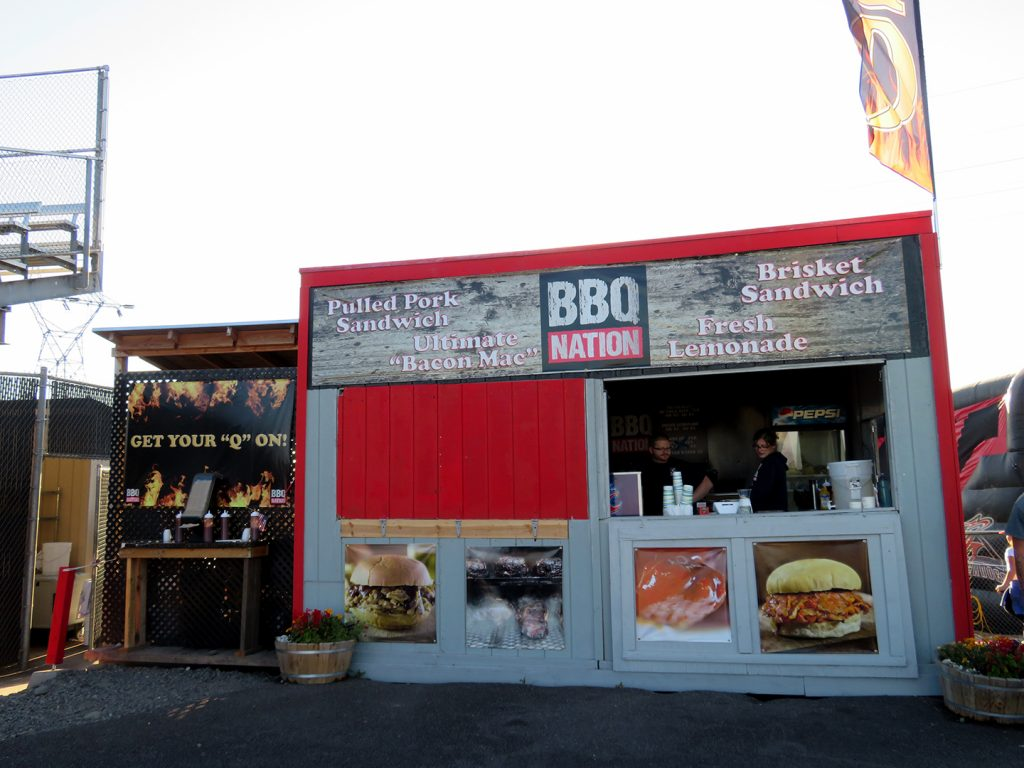 "Wooden concession stand called ""BBQ Nation"" with pictures of barbecue below the window."