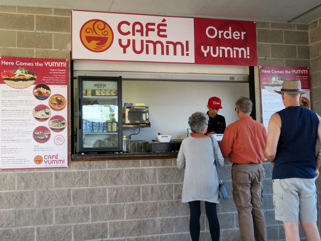 People stand in line at Café Yumm's cinder block concession stand.