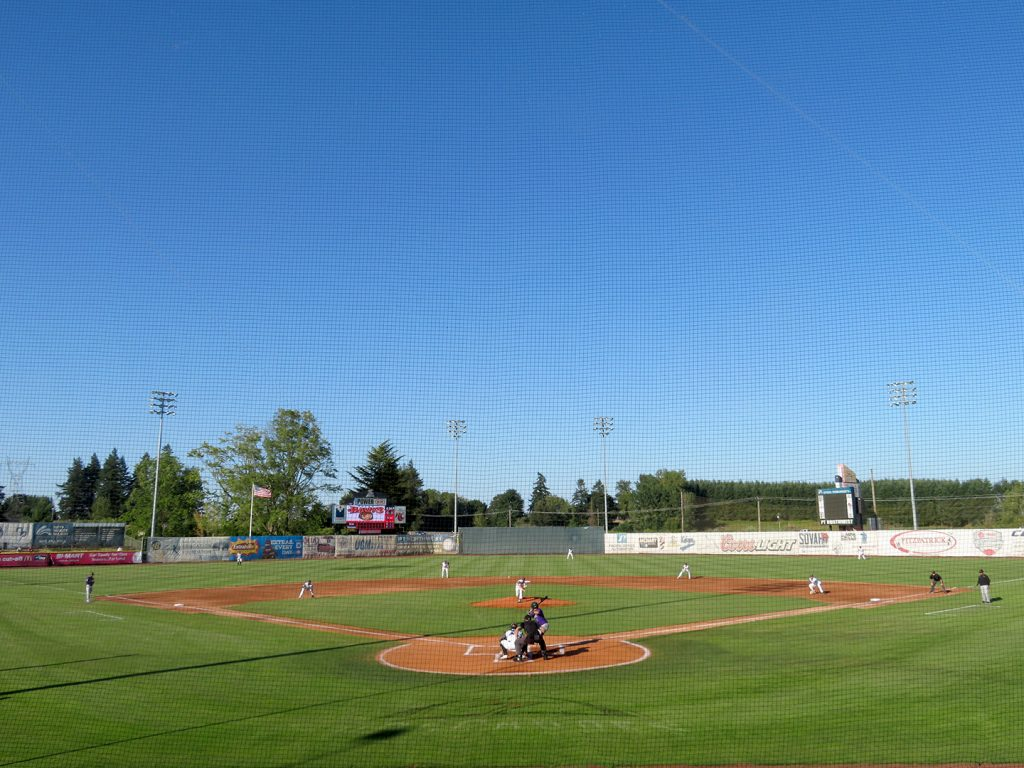Overview of a baseball field as Salem-Keizer Volcanoes right-handed pitcher Conner Nurse delivers the first pitch to Boise Hawks center fielder Isaac Collins.