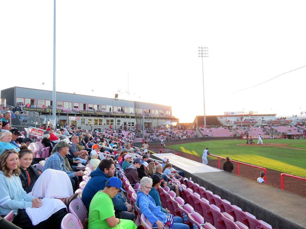 View from first base line of a baseball stadium showing a setting sun in the background and a small one-level seating bowl.