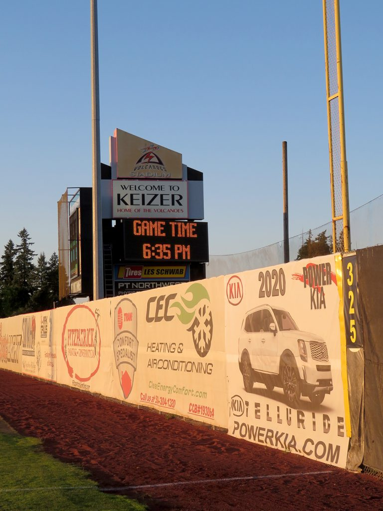 "Outfield wall of baseball stadium with vertical sign behind it that says ""Welcome to Keizer, Home of the Volcanoes."""
