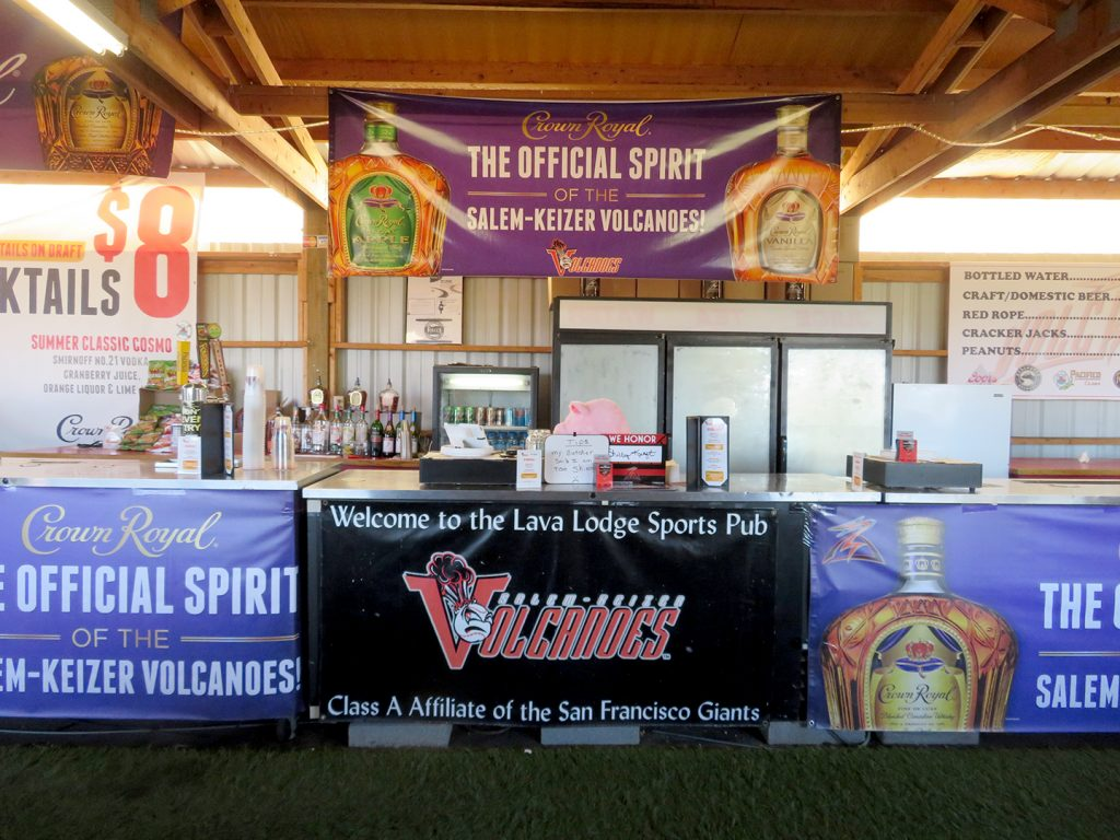 "Artificial grass in front of large bar top with banner that says ""Welcome to the Lava Lodge Sports Pub."""