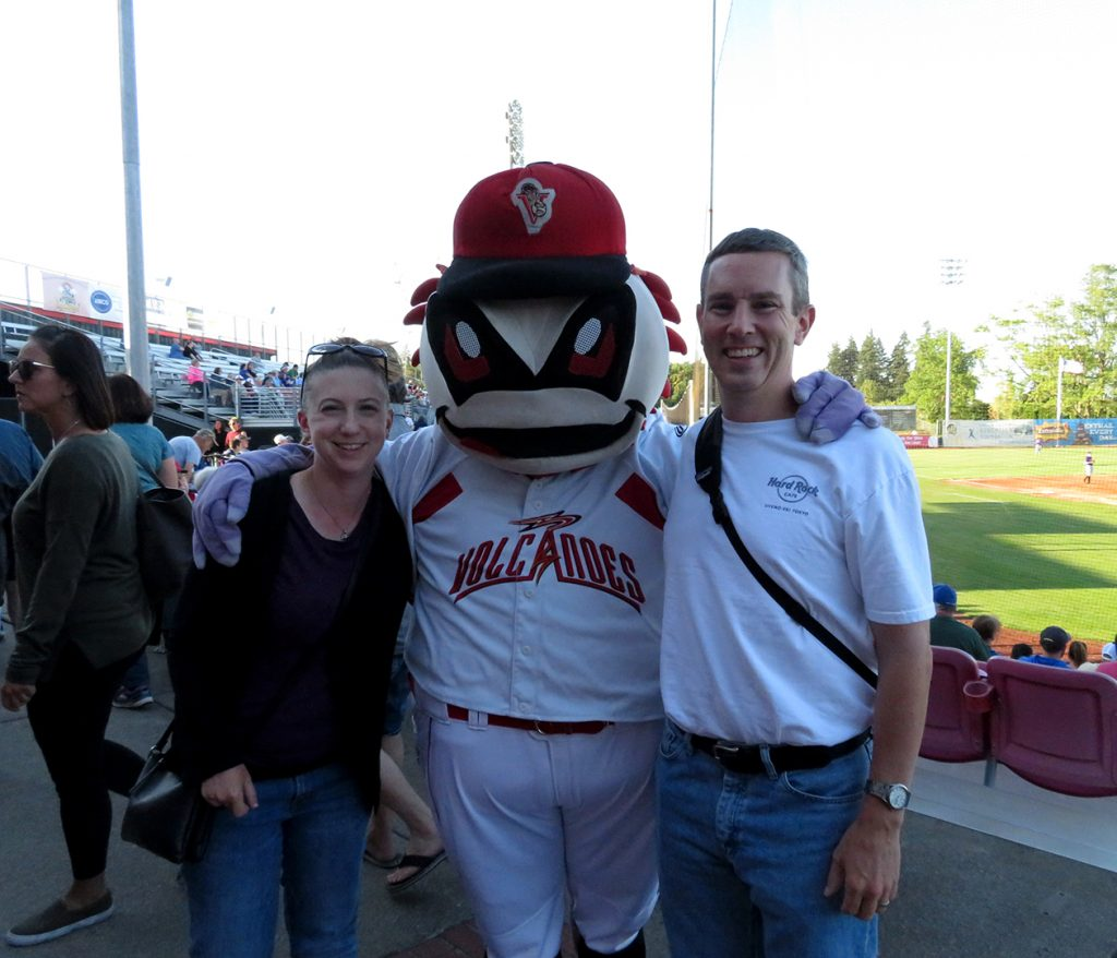 A woman and man stand next to a white dinosaur mascot of the Salem-Keizer Volcanoes.
