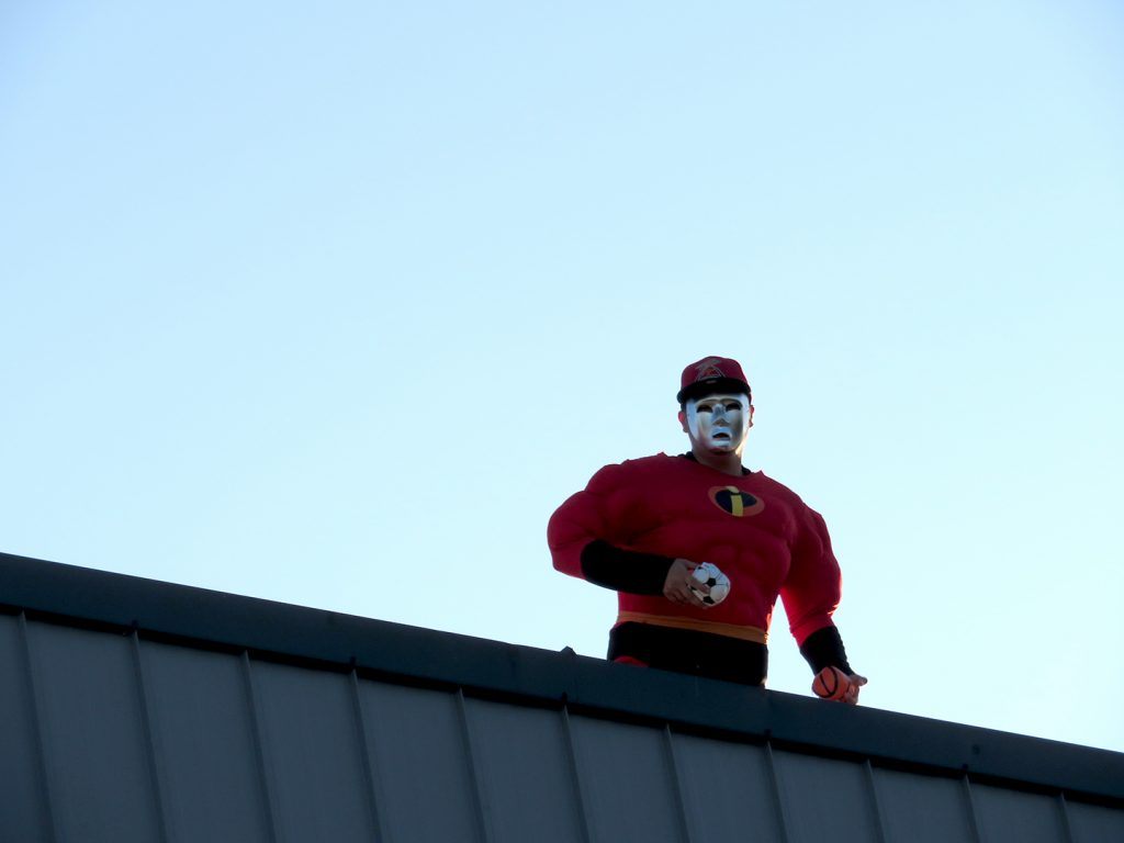 "A man dressed in a Mr. Incredible costume with a silver mask and Salem-Keizer Volcanoes baseball hat known as ""Roof Man"" stands on a roof and throws out giveaway items."