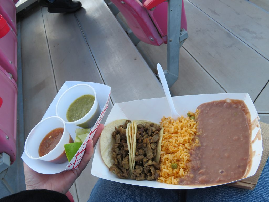 A small paper tray holding green and red salsa next to a larger paper tray holding two steak tacos, Mexican rice, and refried beans.