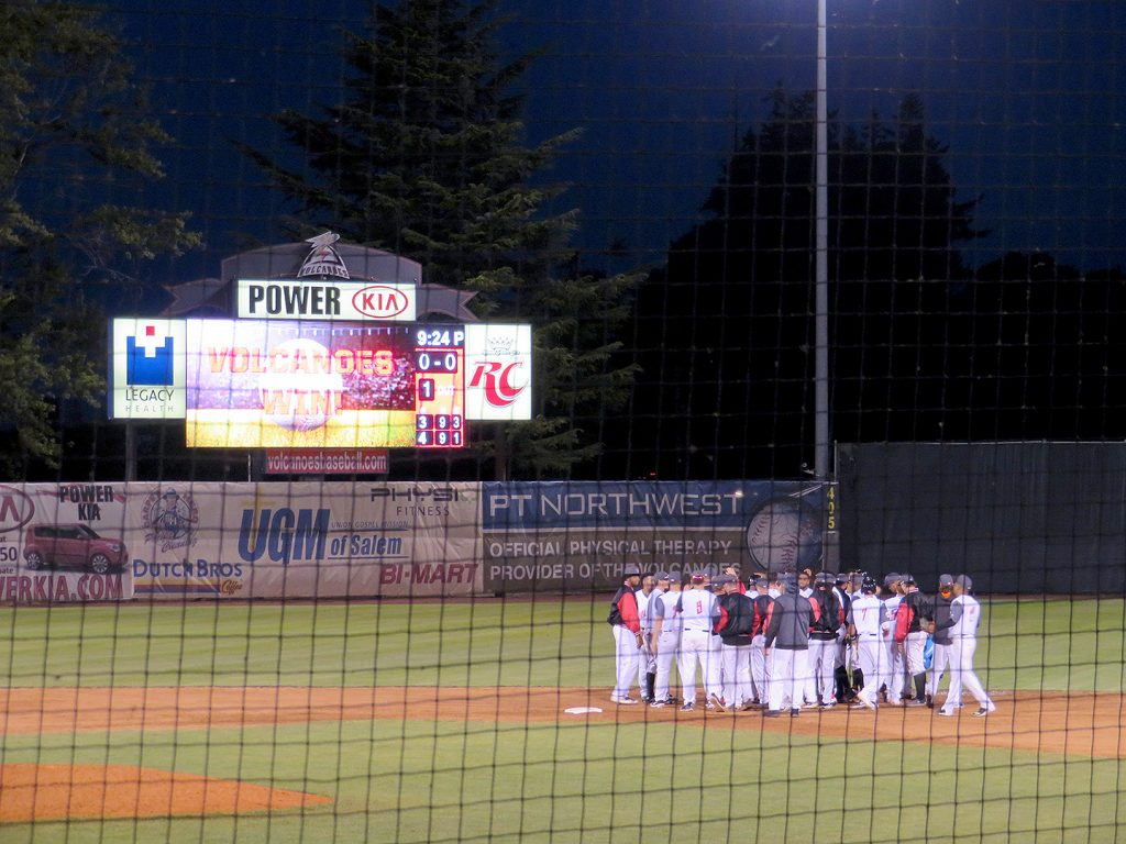 "A small videoboard to the left declares ""Volcanoes Win!"" as a group of baseball players gather on the dirt infield to celebrate the victory."