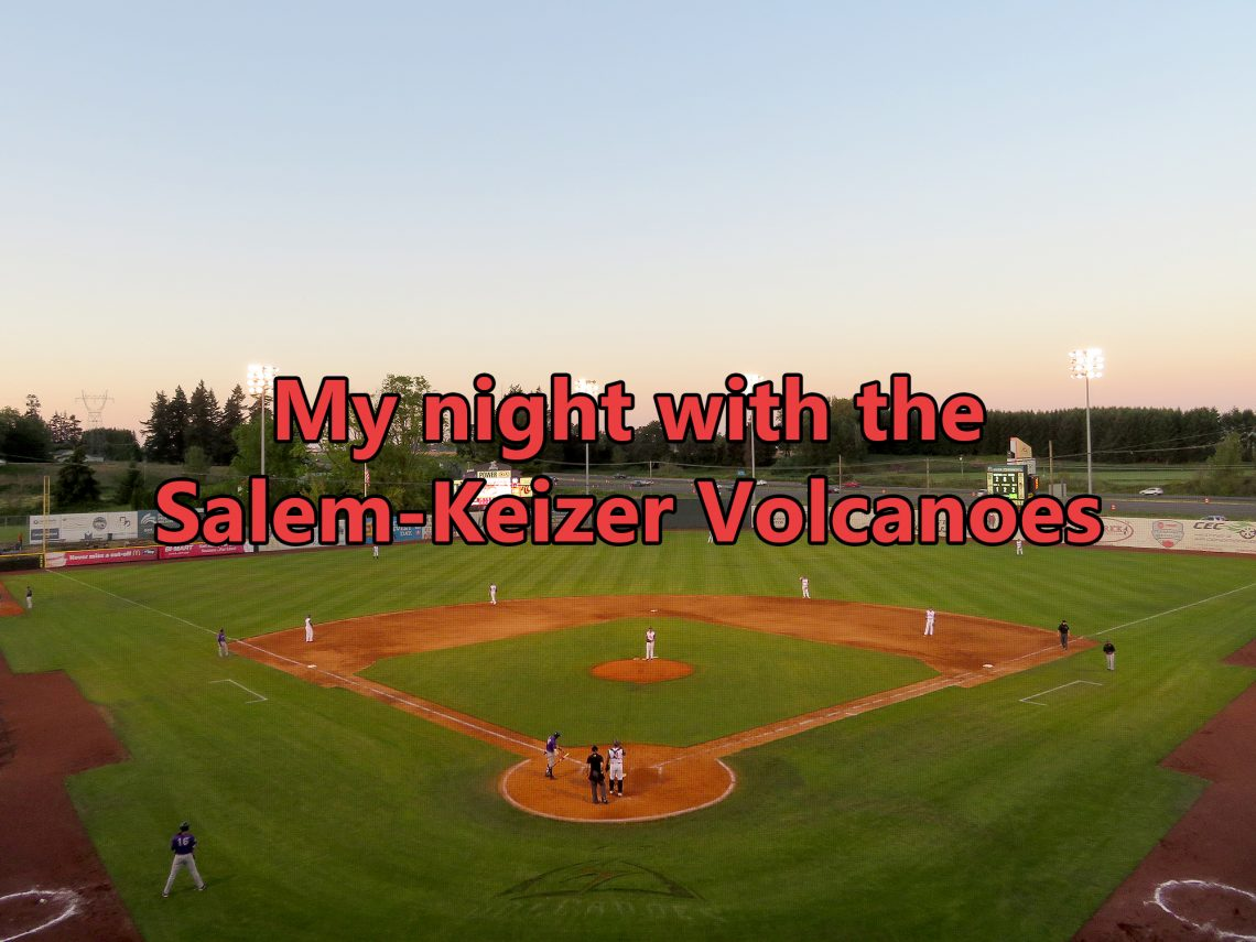 "Aerial overview of a baseball field with an interstate in the background and text overlaying the image that says ""My night with the Salem-Keizer Volcanoes."""