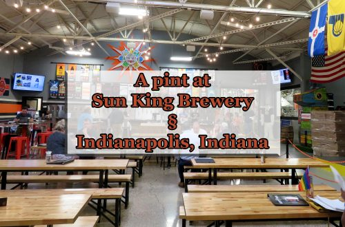 "Overview of a room with several wooden picnic benches and a large bar in the background. Text overlaying image says ""A pint at Sun King Brewery (Section sign) Indianapolis, Indiana."""