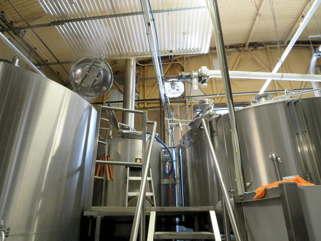 View of two large mash tuns with a platform in the middle creating a 30-barrel brewhouse at Sun King Brewery.