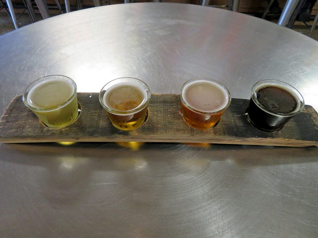 A curved wooden board holding four tasting glasses of beer.