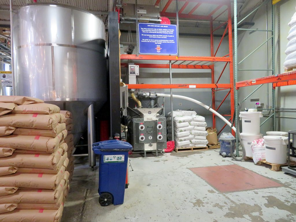 A large stainless steel fermentation tank sits to the left with a grist mill and PVC piping on the right.