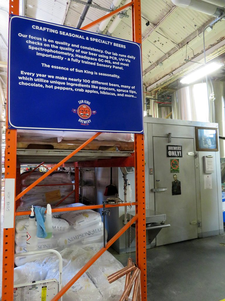 A large blue sign details the focus on Sun King Brewery on seasonal and specialty beers with a large walk-in cooler on the right.