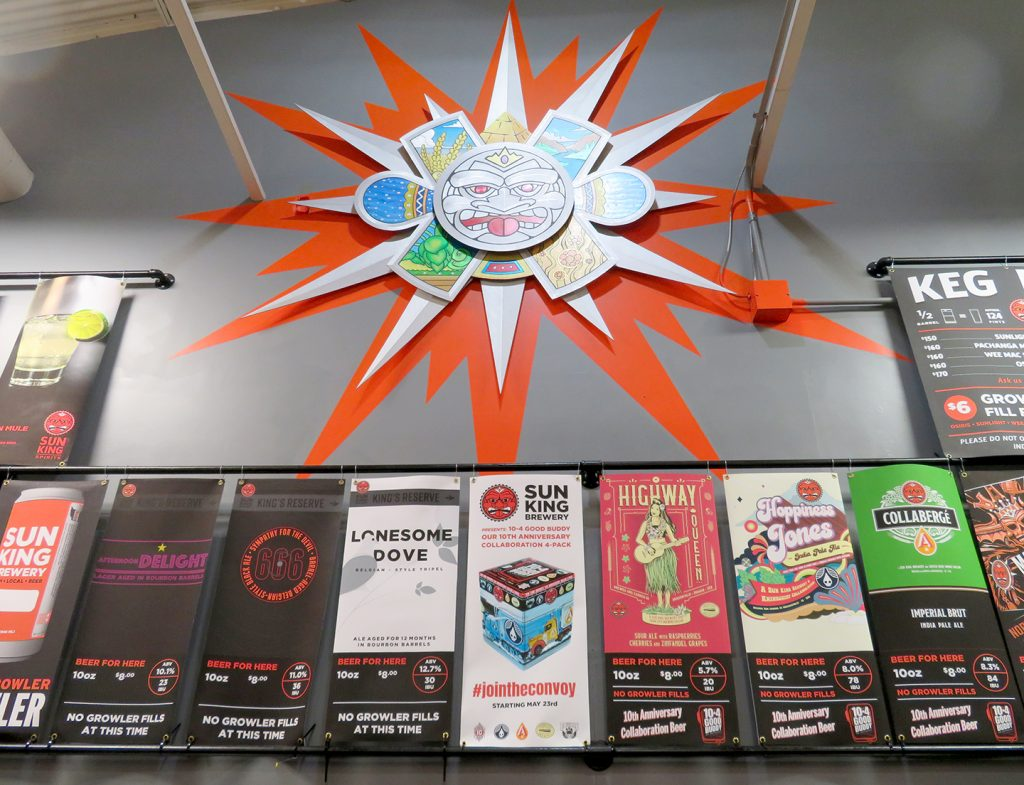 Multiple vertical banners with beer names and colorful designs at Sun King Brewery.
