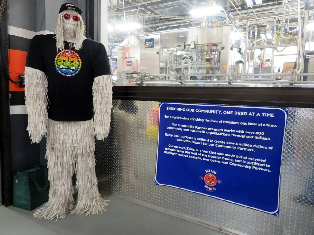 A large yeti made from recycled plastic material standing next to a window that provides a view of the Sun King Brewery production facility.