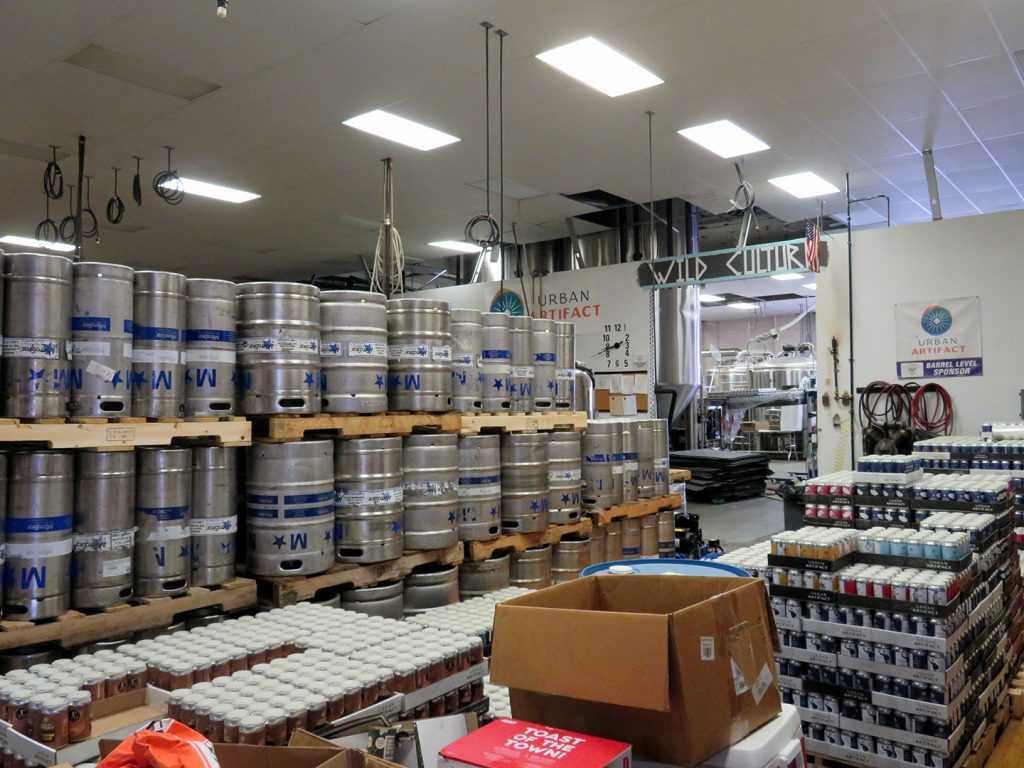 Multiple pallets of kegs are stacked upside down to the left with several cases of beer cans stacked to the right.