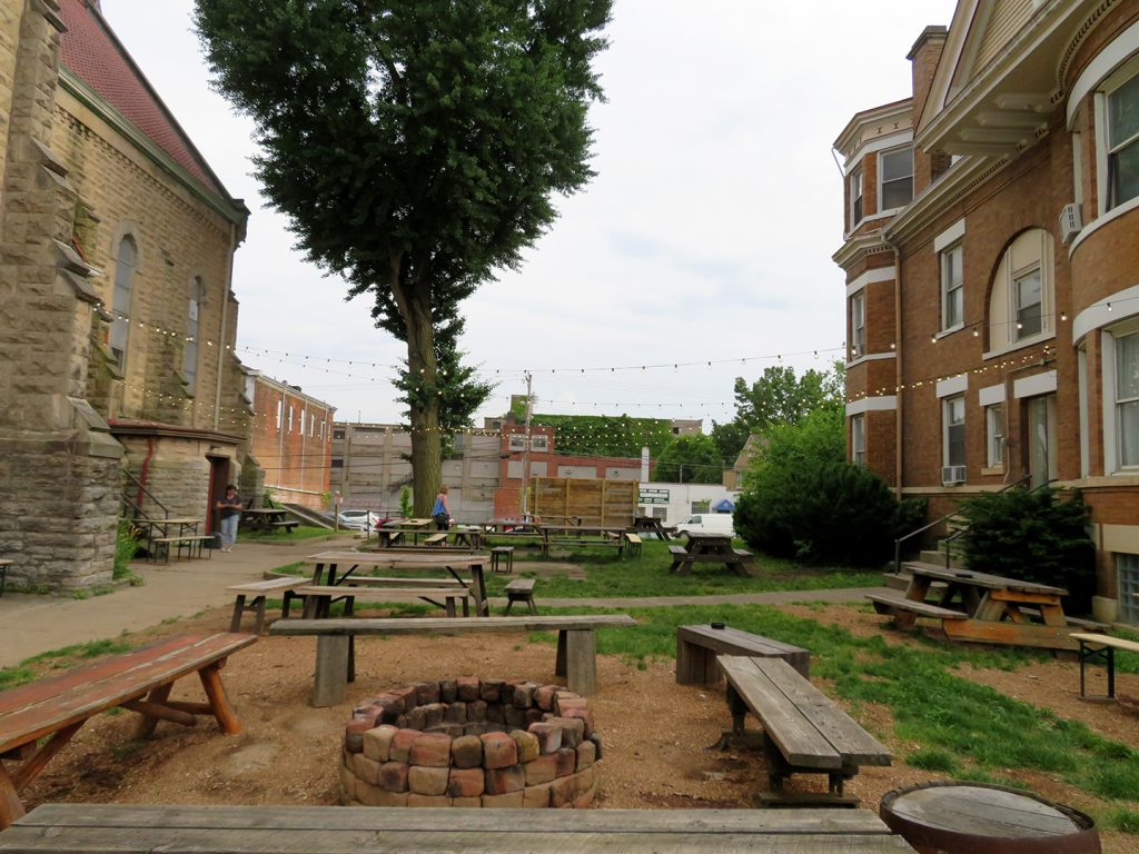A courtyard between a large former church to the left and a brick house on the right.