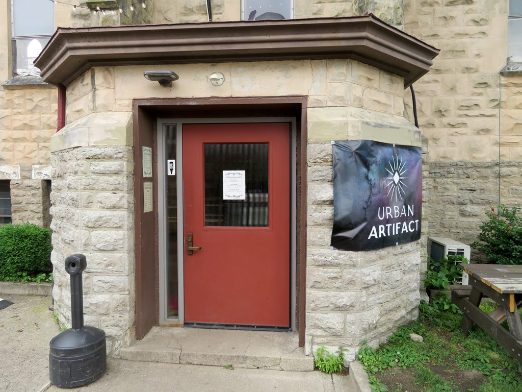 "A red door on an octagonal structure with a black banner on the left side that says ""Urban Artifact."""