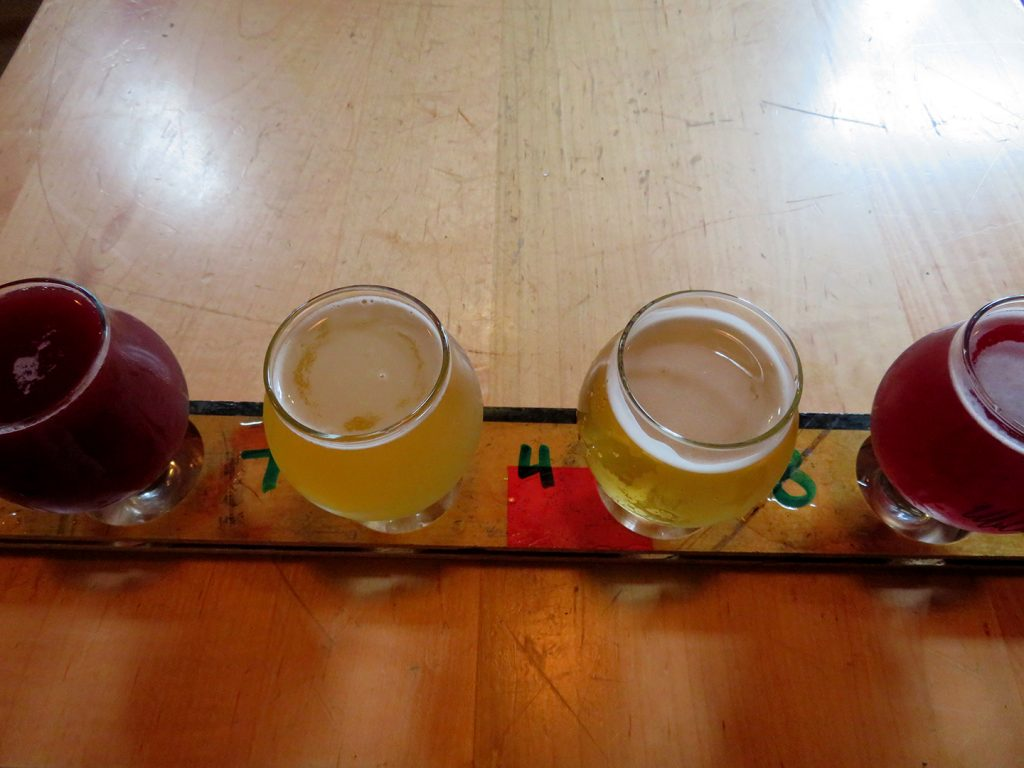 Four small beer tasting glasses on a wooden table.