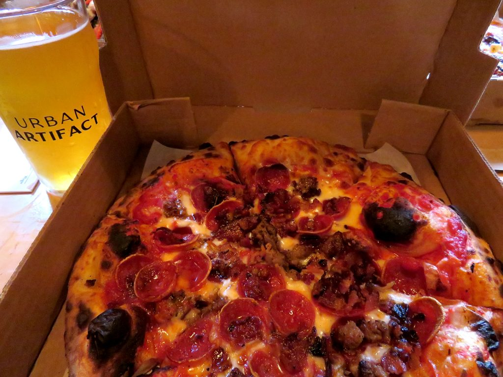 An open pizza box with a personal-size pizza topped with bacon, pepperoni, and sausage and next to a pint glass of beer.