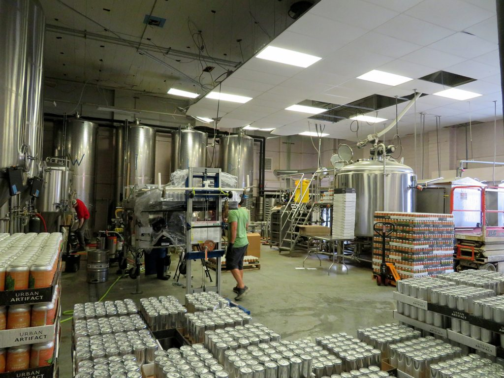 Several cases of beer cans in the foreground with multiple fermentation tanks and a brewhouse in the background.