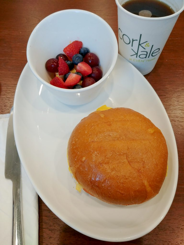 Vertical view of a coffee cup in the background and oval plate with a bowl of assorted fresh fruit and a circular sandwich on the plate in the foreground.