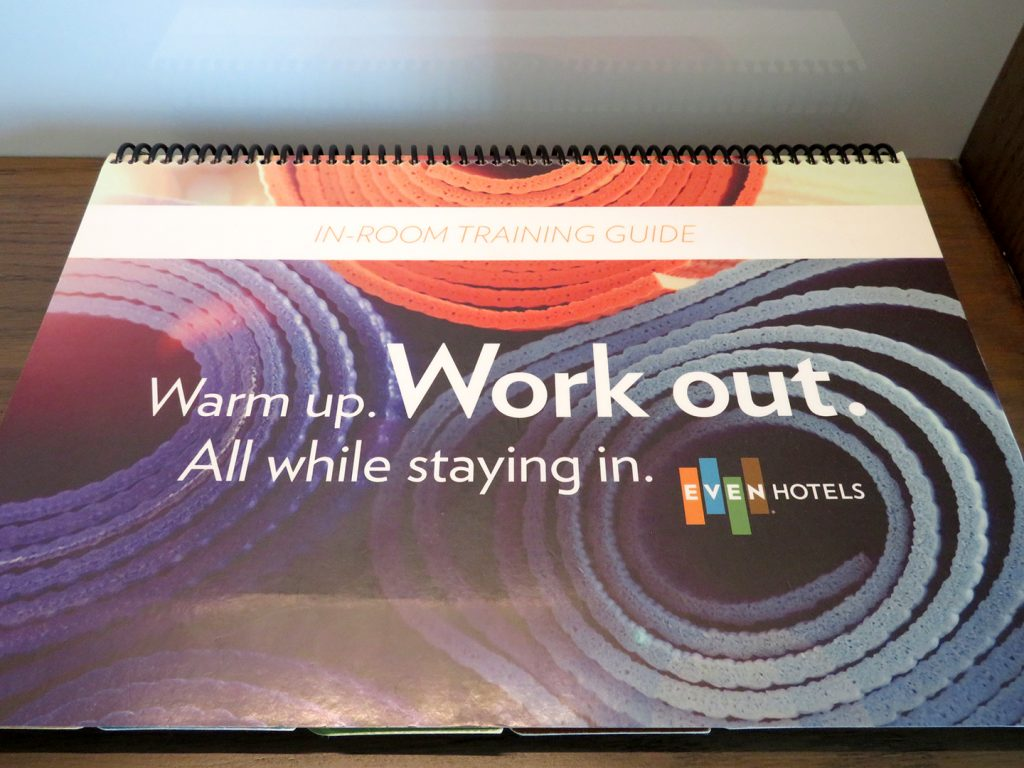 """A horizontal, spiral-bound booklet that shows yoga mats on the cover with text that says """"In-room training guide."""""""