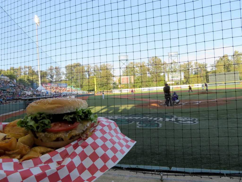 On the left a cheeseburger with lettuce and tomato with a baseball field in the background.