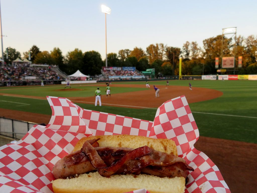 Bratwurst on a big with a strip of bacon and covered with maple syrup with a baseball field in the background.