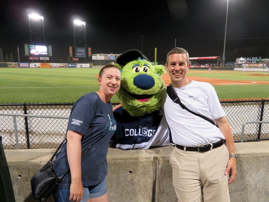 A woman and man stand with a green bear mascot for the Eugene Emeralds called Sluggo.